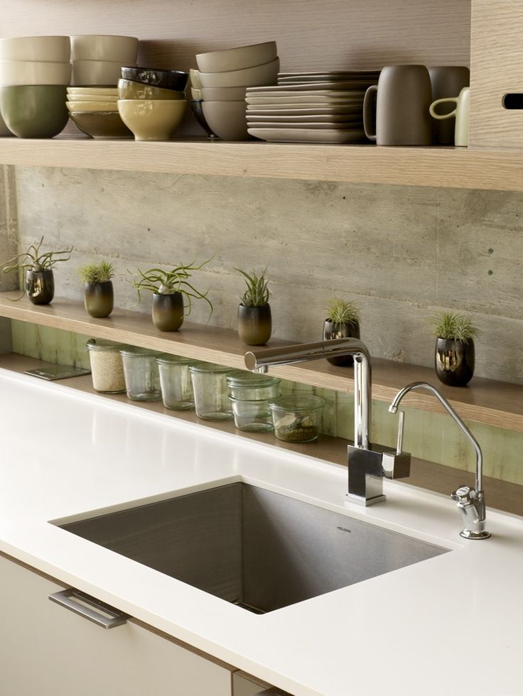 Concrete Backsplash - but more impressed by the first level shelf. Very interesting way to end a worksurface. Can't imagine this comes cheap but with a bit of imagination and this can be recreated for a fraction of the price (excluding the worktop!!!!)