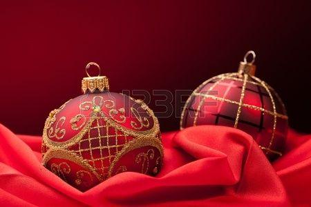 dos bolas de Navidad rojas sobre una tela de seda roja Foto de archivo