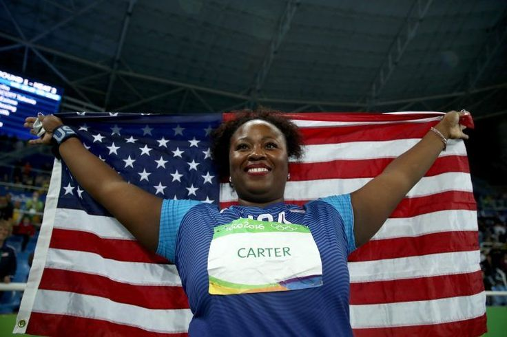 """Michelle Carter carries an American flag after winning gold in the shot put at the 2016 Olympics. Michelle Carter, who calls herself the """"Shot Diva,"""" unleashed a Herculean final throw in the women's shot put competition Friday night in Rio to take home the first-ever gold medal by an American woman"""
