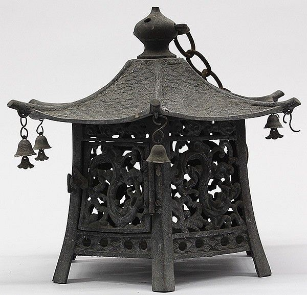 "Description: Japanese bronze hanging lantern, of hexagonal form on six supports with openwork side panels including a hinged door, with a wave pattern on the roof, each corner of the roof with a bell, the finial with a handle and linked to an iron chain (one bell is missing), 10.5""h"