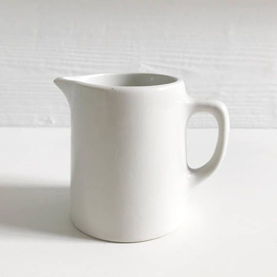 A small white 'Duraline' hotel ware milk jug made in the early 1960s by the English company Grindley. This sweet little jug is in very nice condition with no discernible flaws, chips, cracks or crazing. Lovely to look at and to use. 'Duraline Hotel Ware' was made from vitrified ceramics for the catering industry and was made to last. 7cm high x 8.5cm at its widest point. Due to the difficulty in accurately calculating combined shipping rates I guarantee to refund all shipping overcharges…