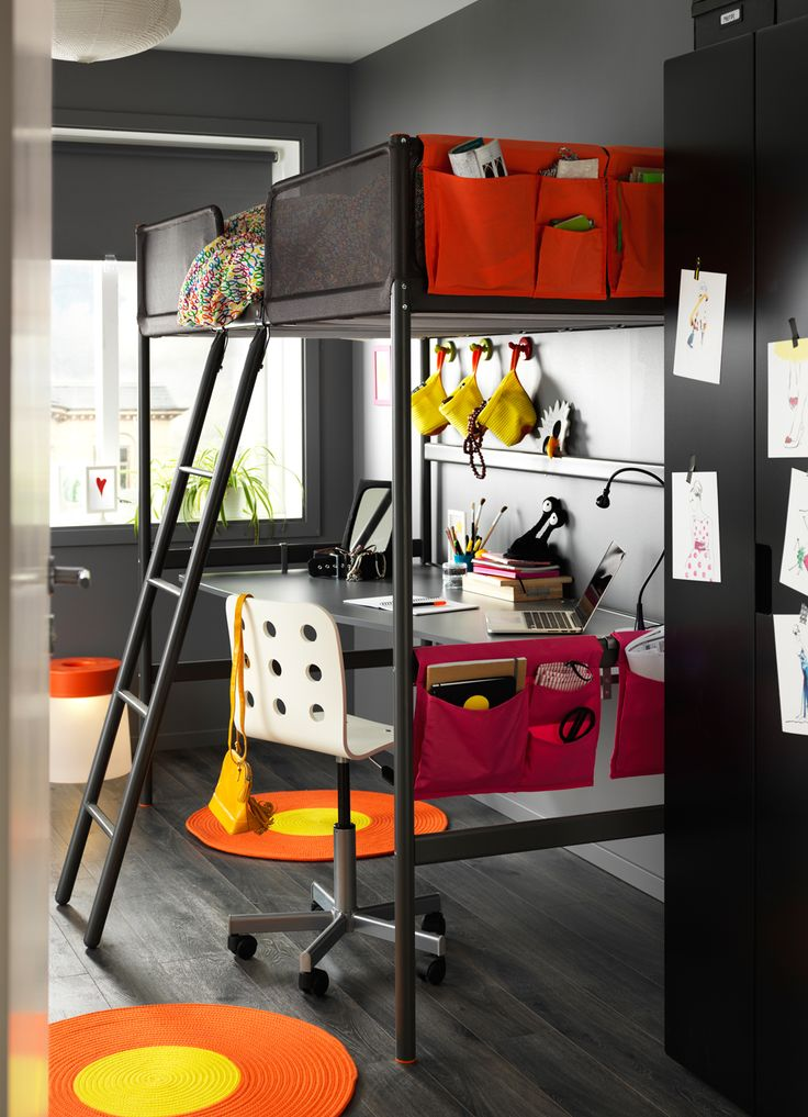 A children's room with a grey loft bed and a silver-coloured desk top underneath. Shown together with bed pockets in orange/pink and braided round rugs in orange/yellow.