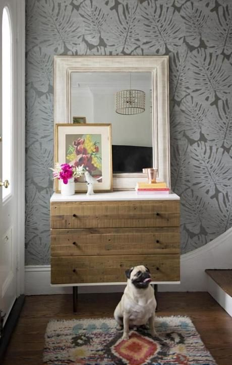 Spaulding created a lovely design moment just inside the front door, the space anchored by an accent wall covered in Jack's Jungle grass-cloth paper by Phillip Jeffries. The family's pug, Vito, sits on an artisan-made rug from West Elm. Vintage artwork from Maureen Dahill's collection adds a spot of color.