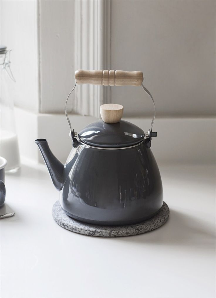 A stove top kettle in a deep charcoal shade of enamel