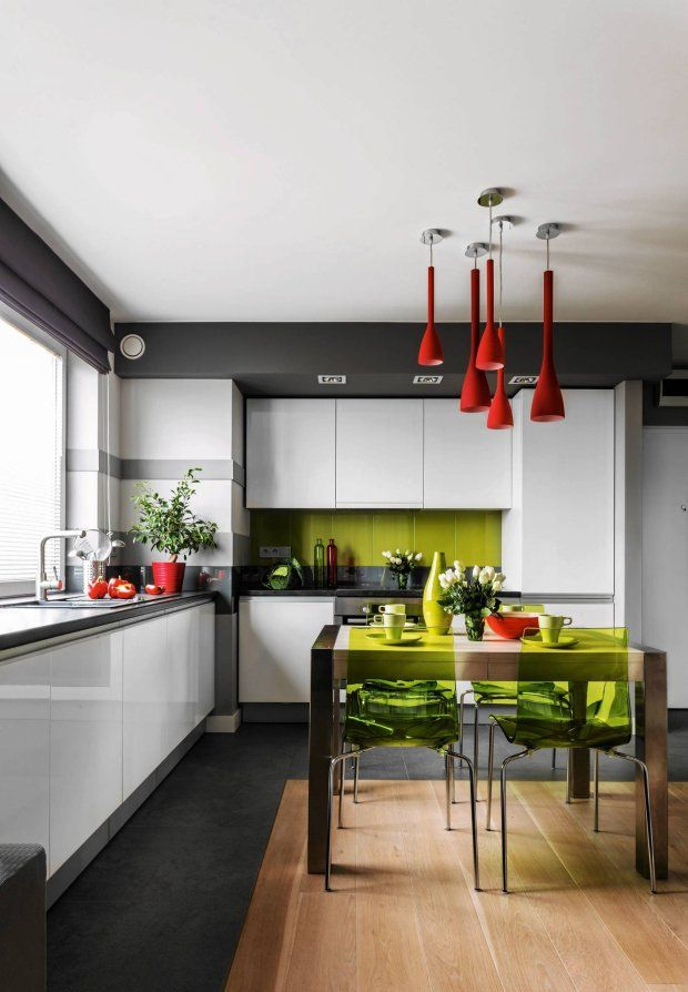Aneks kuchenny, zaaranżowany w bieli i szarościach, nie dominuje nad strefą wypoczynkową. W oczy rzucają się tylko ożywiające tę neutralną kolorystykę plamy soczystej zieleni (płytki nad blatem, krzesła) oraz makowej czerwieni (efektowne lampy na stołem, dekoracyjne dodatki).  Integralną częścią kuchni jest jadalnia, którą wizualnie wyodrębnia podłoga z bielonego dębu. Przy ciągu roboczym położono praktyczny gres.