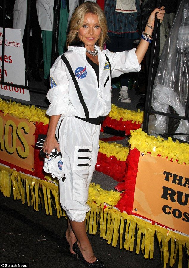 A glamorous astronaut: Kelly Ripa covered up in her Halloween outfit, teamed with full make-up and heels as she acted as Grand Marshall at the Greenwich Village Parade in New York City