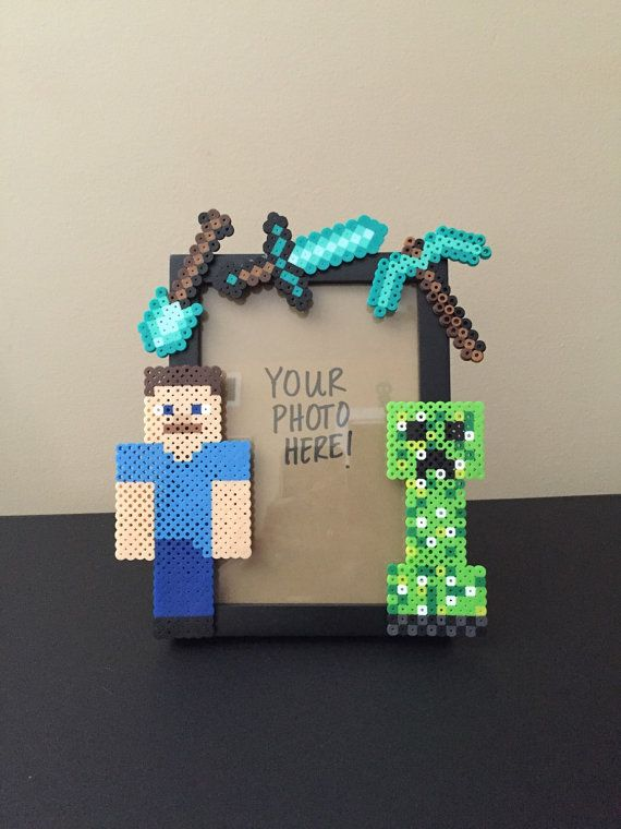 Product Details: This is a handmade Minecraft picture frame! Its perfect for that geeky, loving special someone or friend. The frame is about 7 inches tall and 5 inches wide, which will hold a 5x7 picture. The pieces attached to the frame are made out of plastic beads called Perler Beads. Shipping Information: This item is Made To Order so it may take me a week to process, but I am pretty good with getting it out the next day. I mail these out using USPS Mail which gives you a tracking…