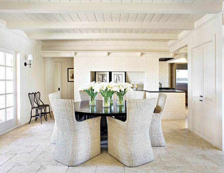 Painted white tongue and groove wood paneling and exposed adobe brick, create this serene and inviting dining space.