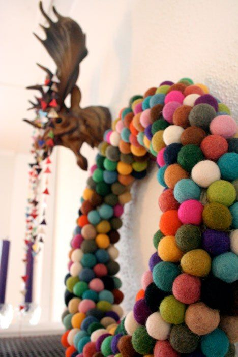Colorful felt balls combing to make the cutest wreath, perfect for a playroom. Get the full tutorial at Wonder How To.    - CountryLiving.com