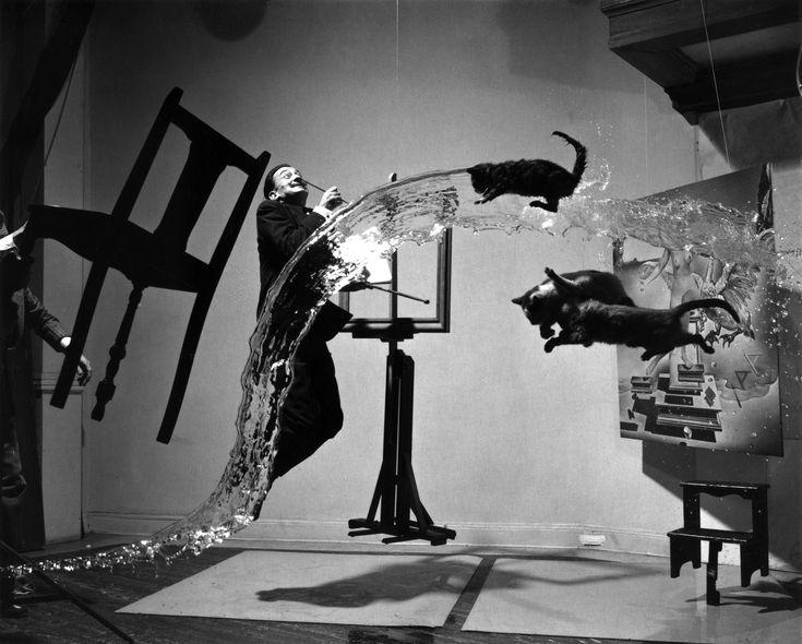 """1948. Uno de los más grandes fotógrafos, Philippe Halsman, congeló el momento en el que Salvador Dalí saltaba en compañía de tres gatos y un balde de agua se cruzaba durante la escena.    Se llevó a cabo en veintiséis intentos y cinco horas para que Halsman obtuviera el resultado deseado. La fotografía se tituló """"Dalí Atomicus"""" debido a """"Leda Atómica"""", el cuadro de Dalí en el que aparece su esposa como Leda. Una copia del cuadro aparece a la derecha, atrás de los gatos."""