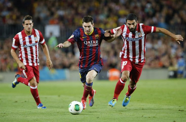 Messi (C) of FC Barcelona duels for the ball with Arda (R) and Koke of Atletico de Madrid during the Spanish Super Cup second leg match between FC Barcelona and Atletico de Madrid at Nou Camp on August 28, 2013 in Barcelona, Catalonia.