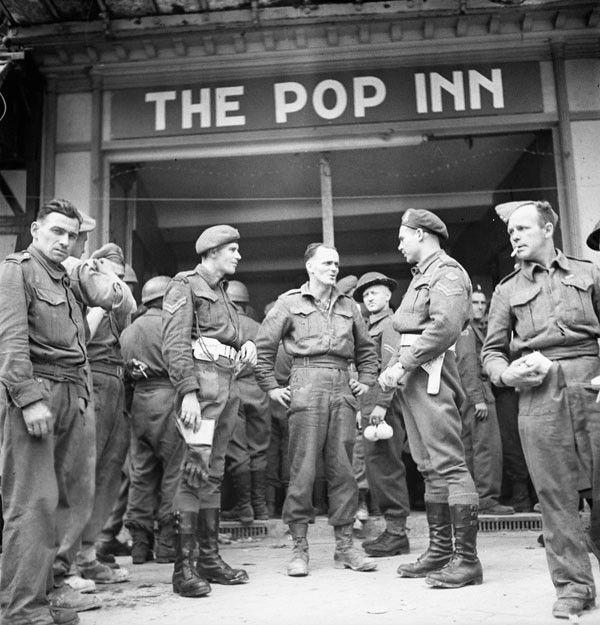 """Caen: au centre deux hommes du Canadian Provost Corps devant """"The Pop Inn"""", la nouvelle cantine du  Navy, Army and Air Force Institute (N.A.A.F.I.), 27 juillet 1944."""