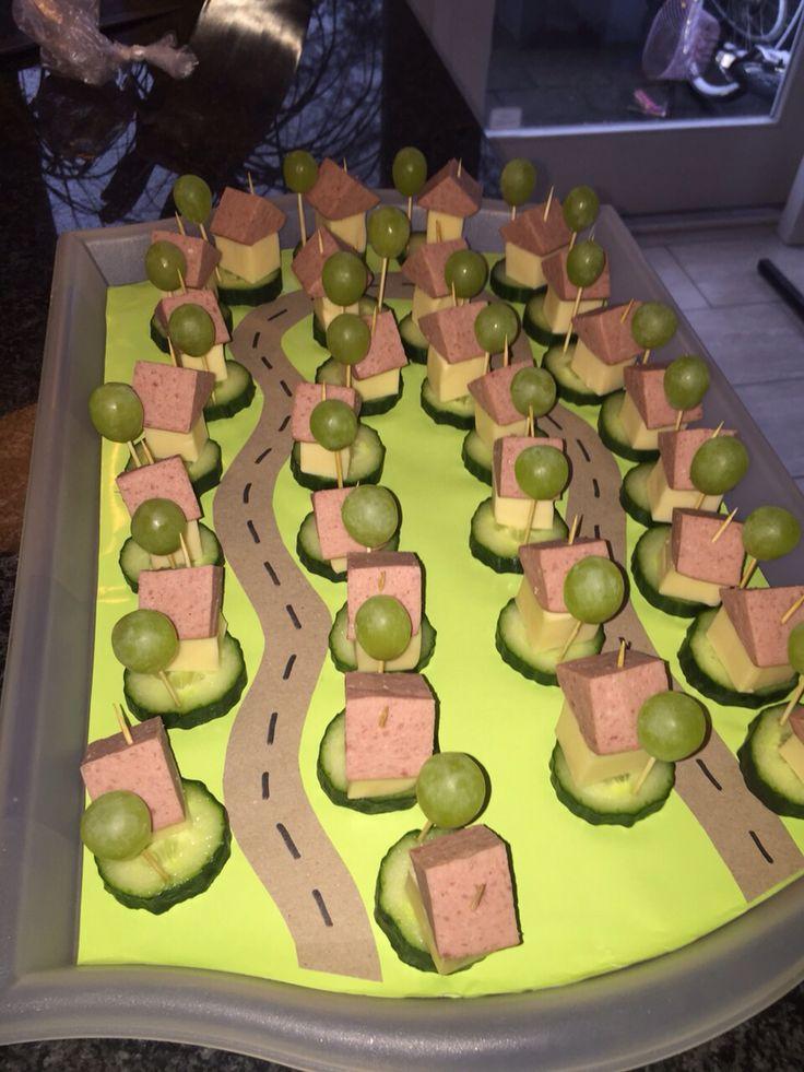 Gezonde traktatie. Huisje met boompje, van kaas, worst, komkommer en druif.