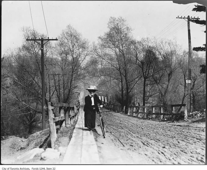 Female cyclist wheeling bicycle up muddy hill on St. Clair Avenue West. – 1907