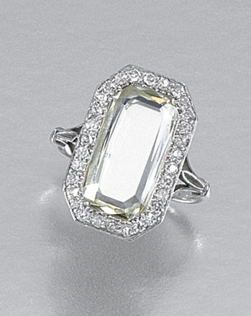 DIAMOND RING, 1920S  centring on a cut-cornered step-cut portrait diamond within a border of circular-cut stones