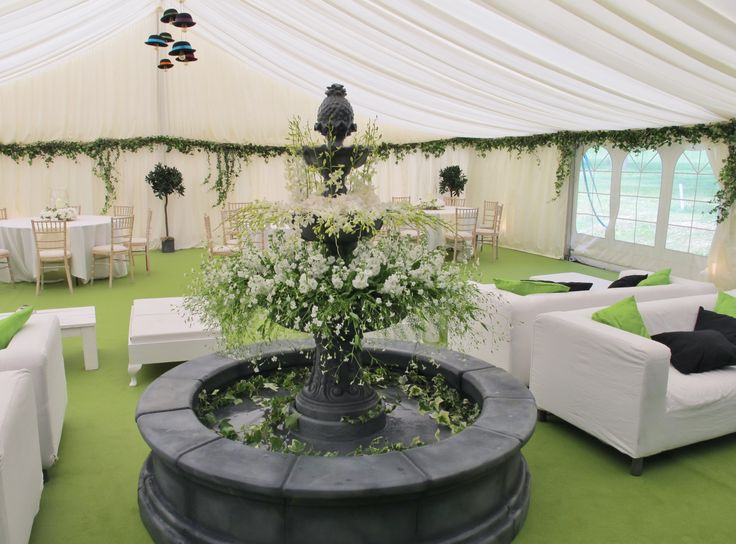 Fountain decorated with flowers for a party in a marquee