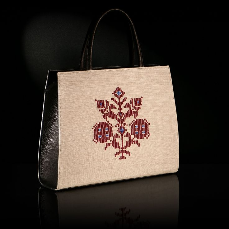 "The woven handmade bag ""Anthemis"" is decorated by a pattern inspired of a traditional outfit from island Astipalaia. Leather's color is black, the background is ecru-beige and the traditional pattern is in deep red shade."