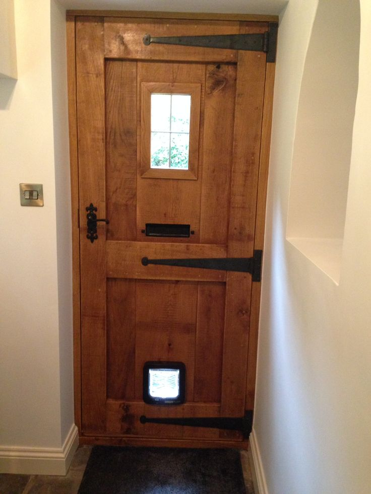 Love the symmetric wood bordering, placement of the peep with the cross hairs, and the hinge metal/wood highlight. Remove the doggie door and mailslot, change orientation to open left. I expect the other side to be plain up and down wood without the wood frame. Ideally raw and then stain to match the garage door.