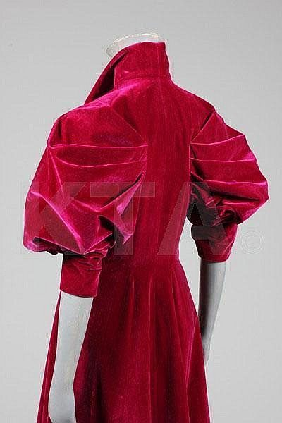 An Elsa Schiaparelli couture deep fuchsia velvet evening coat, late 1930s, bearing printed petersham Paris label and numbered 91184, the front bodice with curved multi-darted seams which sweep down to form a curve at the narrow rear waist, with dramatic fan-shaped pleats forming leg o' mutton sleeves, four large celluloid disc buttons inset with glitter and beads, high stand angular collar, silk lining, chest approx 86cm, 34in