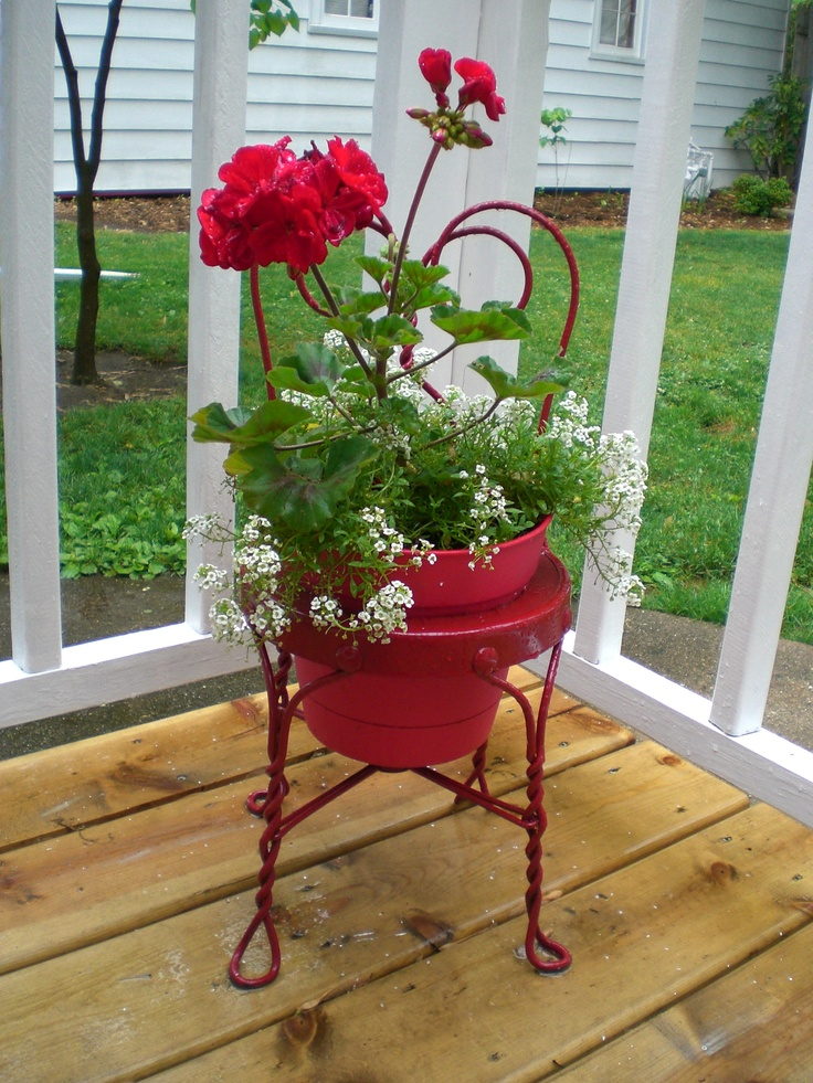 My Hubby bought this mini ice cream chair at an antique store, cut the bottom out, painted it red and added a flower to grace our back steps. We just think it`s too cute!