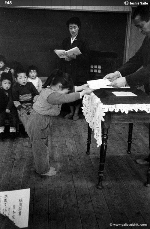 Children in 1950s Japan. Toshie Saito. Tiny girl bowing as she hands in or takes paper from teacher.