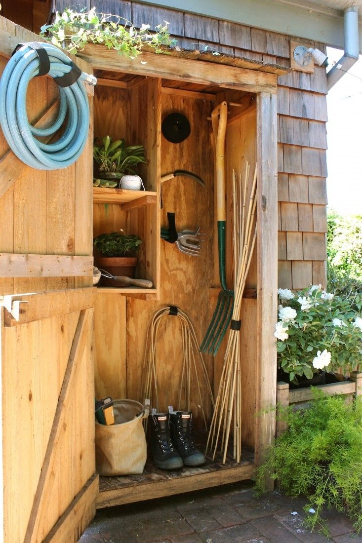 An outdoor closet for gardening equipment with pegs and shelves for hose, tools, and boots. Gardenista.