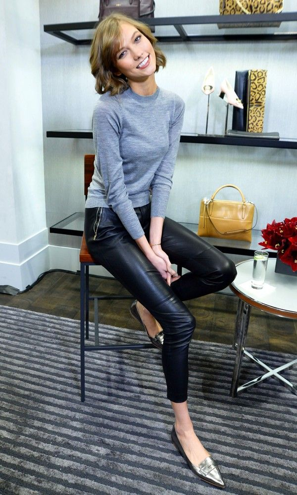 Karlie Kloss in a polo neck grey top, black leather trousers & glammed up the look with pointed metallic flats shoes