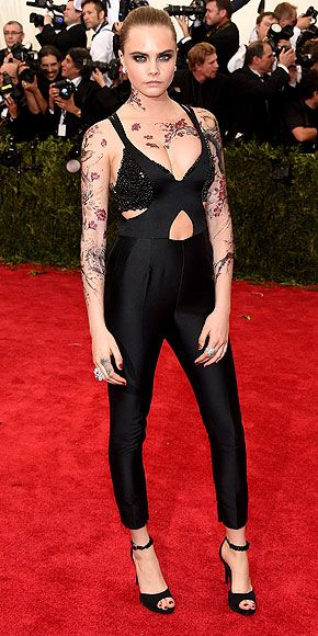 The Most Jaw-Dropping Dresses at the 2015 Met Gala | CARA DELEVINGNE | in a black Stella McCartney jumpsuit featuring a bra top and skinny pant, ankle strap pumps (also Stella), Cartier jewels and and (fake) floral body tattoos.