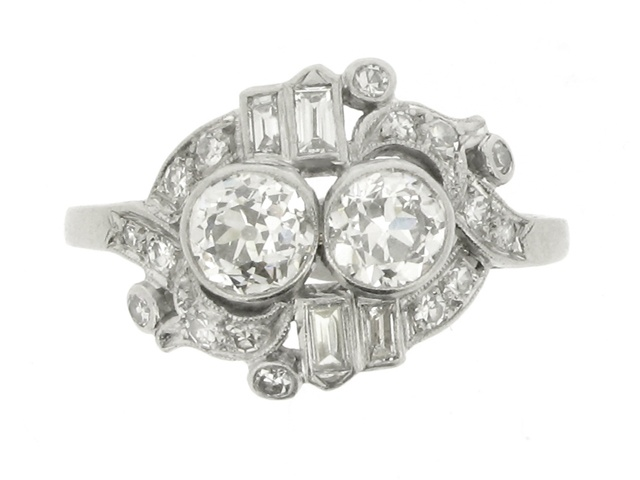 Ornate two stone diamond cluster ring, American, circa 1935. A platinum and iridium ring horizontally set with two round old cut diamonds in millegrain collet settings with an approximate total weight of 1.00 carats, surrounded by a scrolling pierced bezel set with four rectangular baguette cut diamonds in rubover collet settings with an approximate total weight of 0.20 carats, and sixteen round eight cut diamonds in millegrain bead settings with an approximate total weight of 0.40 carats…