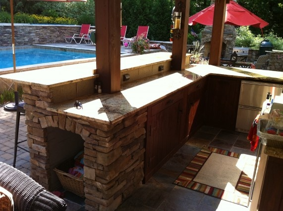 outdoor kitchen with bar by signature outdoor concepts