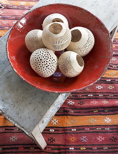 Seasons: Mooi opengewerkte kokosnoten krijgen een nieuwe functie als waxinelichthouders.  Waxinelichthouders, € 13,50 (Manggis Living). Rode metalen schaal, € 22,50, tafel met metalen blad, € 250,- en gestreepte kelim, € 605,- (Raw Materials).  Fotografie Albert Roosenburg   Styling Annelies Morris