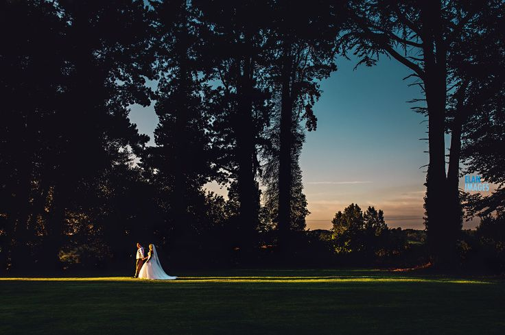 Bride and groom enjoying a walk in the last of the evening sun during their wedding at Coombe Lodge in Blagdon.