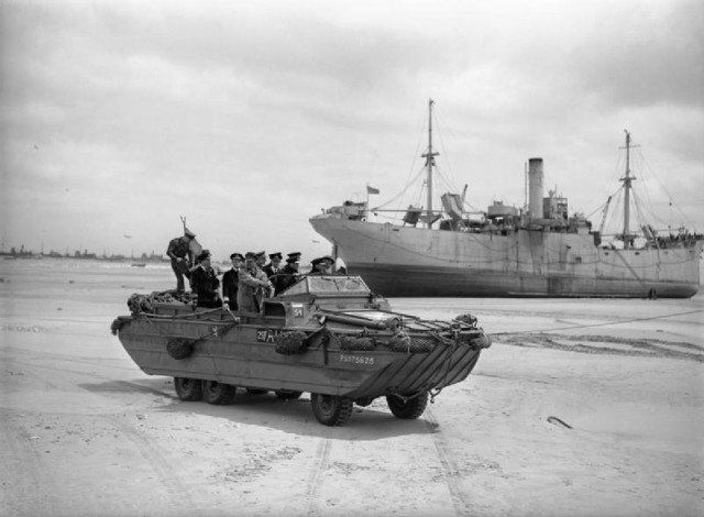 King George VI, accompanied by Admiral Sir Bertram Ramsay and the First Sea Lord, Admiral Sir Andrew Cunningham, touring the beaches at Normandy in a DUKW amphibious vehicle, 16 June 1944
