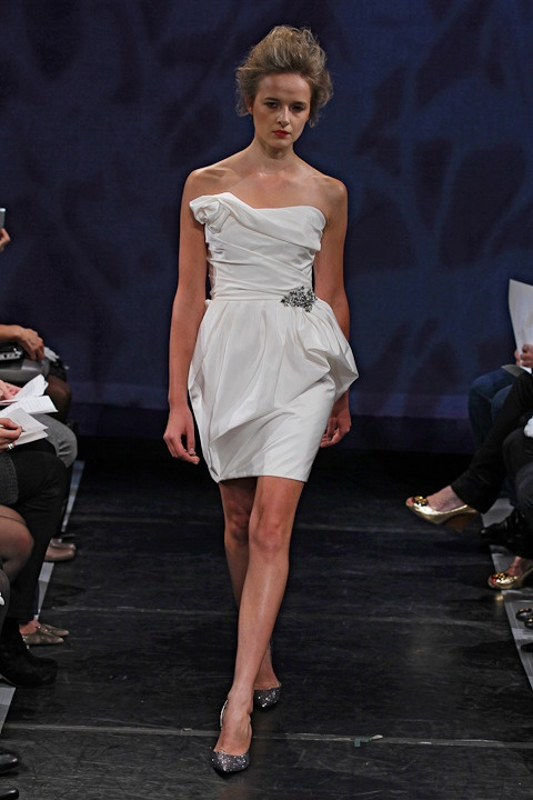 GIGI, RIVINI by Rita Vinieris - This little white dress has an asymmetrical, delicately gathered peplum, accented with a crystal beaded appliqué. The asymmetrical draped bodice finishes into a neckline rosette.