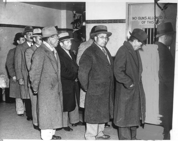 """""""This contingent of Santa Barbara County Japanese, who were rounded up in alien enemy raids under direction of FBI, shown leaving county jail yesterday en route to Midwest internment camps.""""--caption on photograph"""