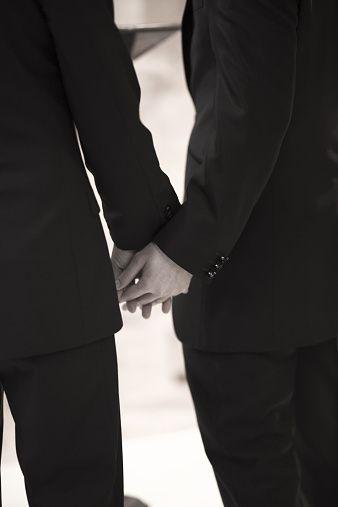 Bridegrooms in gay wedding holding hands