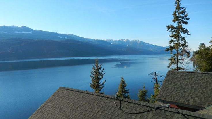 Like this home view? The cystal clear lake view, the mountains, the evergreens! This lakefront property is for sale with log homes. #lakefronthomesforsale #propertyforsale