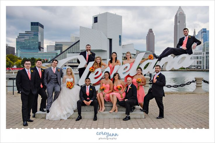Coral and black wedding party portrait in Downtown Cleveland at the E 9th Street Pier Cleveland script sign.