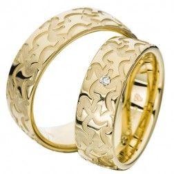Vielses- og forlovelsesringe i guld  Ringene er 7,0 mm brede og er 2,0 mm høje. Profilen er let afrundet udvendigt og indvendigt. Designet består af en blankpoleret overflade med et silkemat, rillet mønster.  Dameringen er isat en brillant på 0,03 ct. W/IF kvalitet placeret midt på ringen.  www.fredberg.com