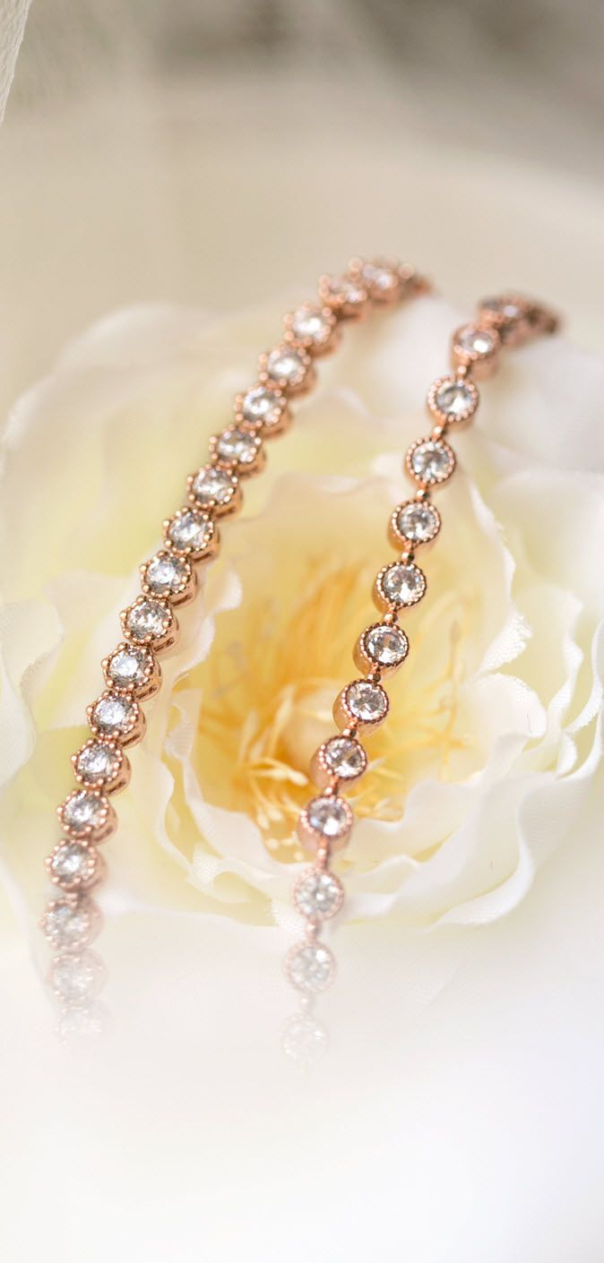This rose gold tennis bracelet is the perfect wedding accessory. This piece is 18K Rose Gold plated and made with sparkly Cubic Zirconia crystals. Make a statement while completing your bridal look wi