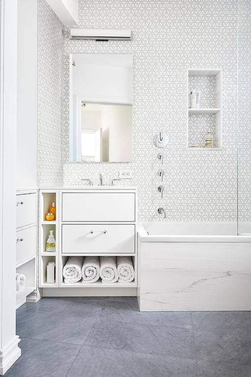 A classic white and gray mosaic shower tile is the perfect counterpoint to a more modern mosaic pattern in the shower that surrounds this bathroom.