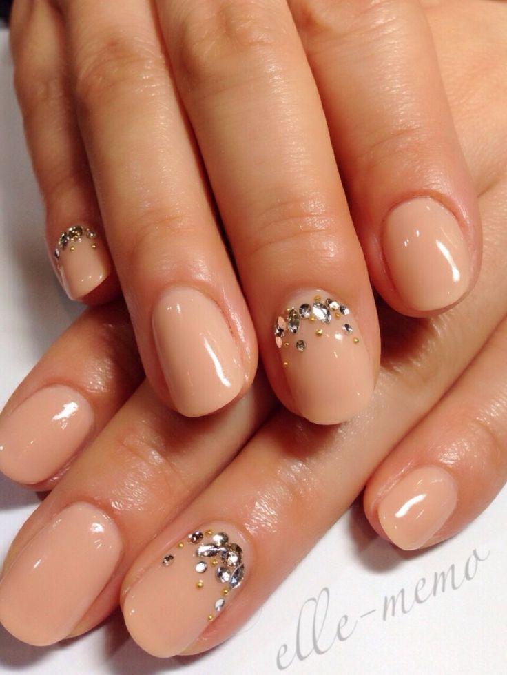 Uñas en beige, algunas de ellas decoradas con brillos cristalinos y dorados.