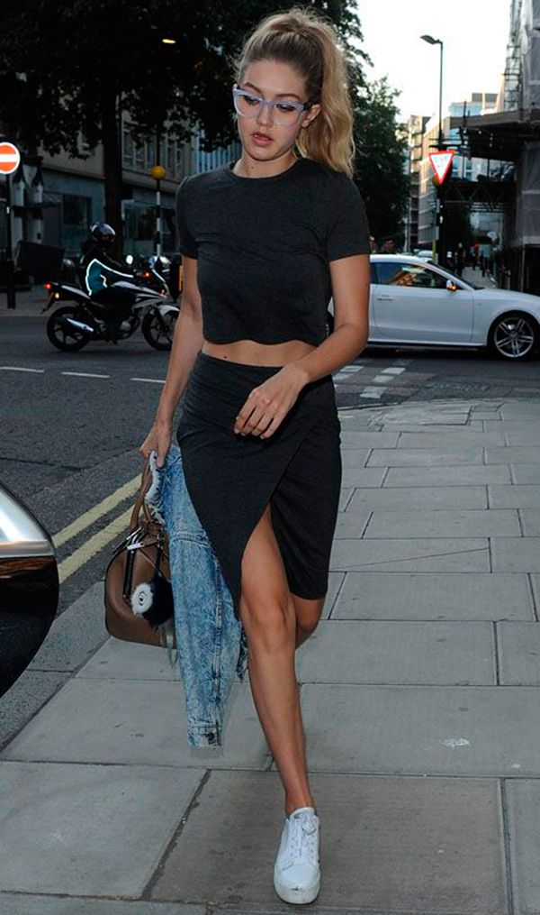 Gigi Hadid veste t-shirt cropped, saia assimétrica preta, tenis branco e jaqueta jeans