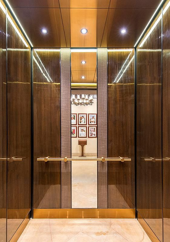 LEVELe-105 Elevator Interior with customized panel layout; panels in custom American Cherry with Dark Mahogany Stain wood veneer, Bonded Bronze with Dark Patina and Charleston pattern, laminated glass mirror; Compass handrail at The Pavilion at DLF Golf & Country Club, Gurgaon, Haryana, India