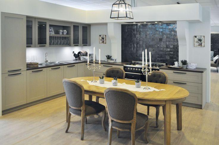Prachtige, landelijke keuken met keukenkasten in een beige kleur. De muur aan de kookplaat is samengesteld met zwarte mozaïektegels, wat zorgt voor een extra eyecatcher