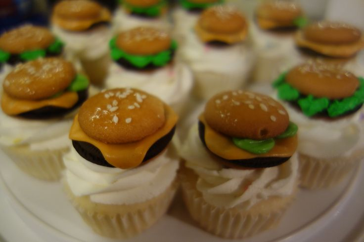 """Mini """"hamburger"""" cupcakes.  Use Vanilla wafers for the buns, Oreo thins for the meat, softened flavored Tootsie rolls for cheese and pickles. Green buttercream for lettuce.  Brush tops with corn syrup to hold the sesame seeds.  Stick it all together with buttercream.  Cute and easy!"""