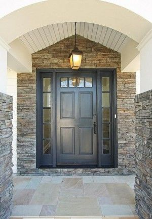 A house with a stone exterior. The main entrance has an arched stoop roof with…