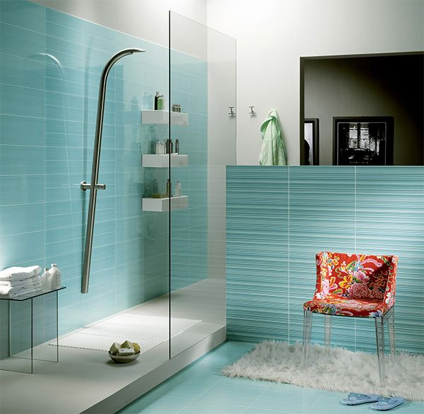 Amazing Blue bathroom with shower cabin. Colorful splash of the chair pairs perfectly with the turquoise tiles.