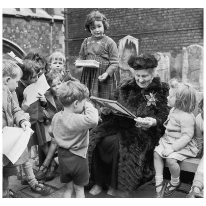 A classic photo of Maria Montessori reading to children. Used for display in the classroom or the office.