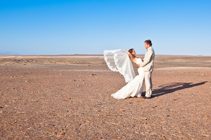 Bare Namibian landscape with beautiful lace veil that makes the bride look like a butterfly taken by Veronique-Photography